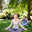 Couple practicing yoga in the park — Photo