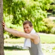 Man doing his stretches in the park - Stock Photo