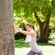 Woman doing her stretches in the park - Stock Photo