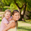 Beautiful mother giving daughter piggyback — Stock Photo #10859431