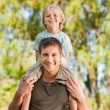 Happy father giving son piggyback — Stock Photo #10859476
