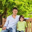 Foto Stock: Father with his son on the bench