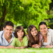 Family lying down in the park — Stock Photo