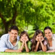Family lying down in the park — Stock Photo #10859794