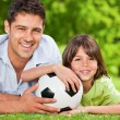 Father and his son with their ball in the park — Stock Photo