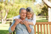 Senior woman hugging her husband who is on the bench — Stock Photo