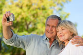 Smiling couple taking a photo of themselves in the park — Stock Photo
