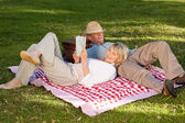 Woman reading while her husband is sleeping in the park — Stock Photo