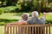 Casal sentado no banco com as costas para a câmera — Foto Stock