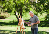 Senior man painting in the garden — Stok fotoğraf