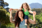 Woman giving daughter a piggyback — Stock Photo
