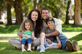 Happy family sitting in the garden — Stock Photo