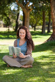 Woman reading a book in the garden — Stock Photo