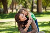 Mujer abrazando a su hija en el parque — Foto de Stock