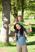Mother giving daughter a piggyback — Stock Photo