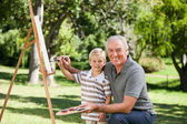Happy Grandfather and his grandson painting in the garden — Stok fotoğraf