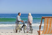 Elderly couple with their bikes on the beach — Zdjęcie stockowe