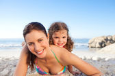 Mother and daughter lying down on the beach — Stock Photo