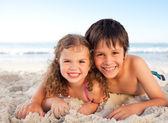 Mały chłopiec i jego siostra, leżenie na plaży — Zdjęcie stockowe