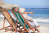 Retired couple sitting on deck chairs — Stock Photo