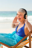 Retired woman listening to music at the beach — Stock Photo