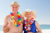 Senior couple drinking a cocktail on the beach — Stock Photo