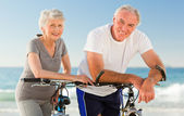Retired couple with their bikes on the beach — Stok fotoğraf