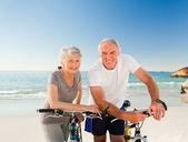 Pensionerat par med sina cyklar på stranden — Stockfoto