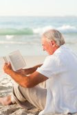 Man reading a book on the beach — Stock Photo