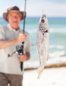 Man fishing at the beach — Stockfoto