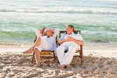 Elderly couple relaxing in their deck chairs — Stock Photo
