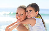 Mother having daughter a piggyback at the beach — Stock Photo