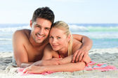 Lovers lying down on the beach — Stock Photo