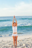 Woman practicing yoga on the beach — Photo
