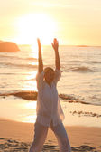 Woman practicing yoga during the sunset — Stock Photo