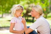 Mutter und tochter riechen eine blume — Stockfoto