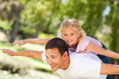 Little girl playing with her father in the park — Stock Photo
