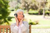 Äldre kvinna lyssna på lite musik — Stockfoto