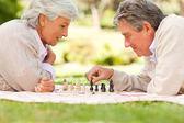 Elderly couple playing chess — Stock Photo