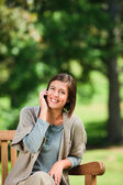 Beautiful woman phoning on the bench — Stock Photo