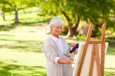 Senior woman painting in the park — Stock Photo
