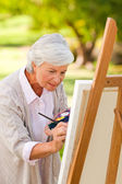 Mature woman painting in the park — Stock Photo