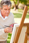 Elderly man painting in the park — Stock Photo