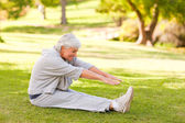 Retired woman doing her stretches in the park — Stock Photo