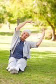 Senior woman doing her stretches in the park — Stock Photo