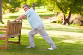 Retired man doing his stretches in the park — Stock Photo