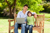 Son with his father looking at their laptop — Stockfoto
