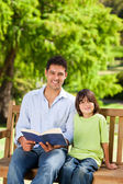 Son with his father reading a book — Stock Photo