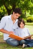 Figlio con il padre guardando le loro foto album — Foto Stock