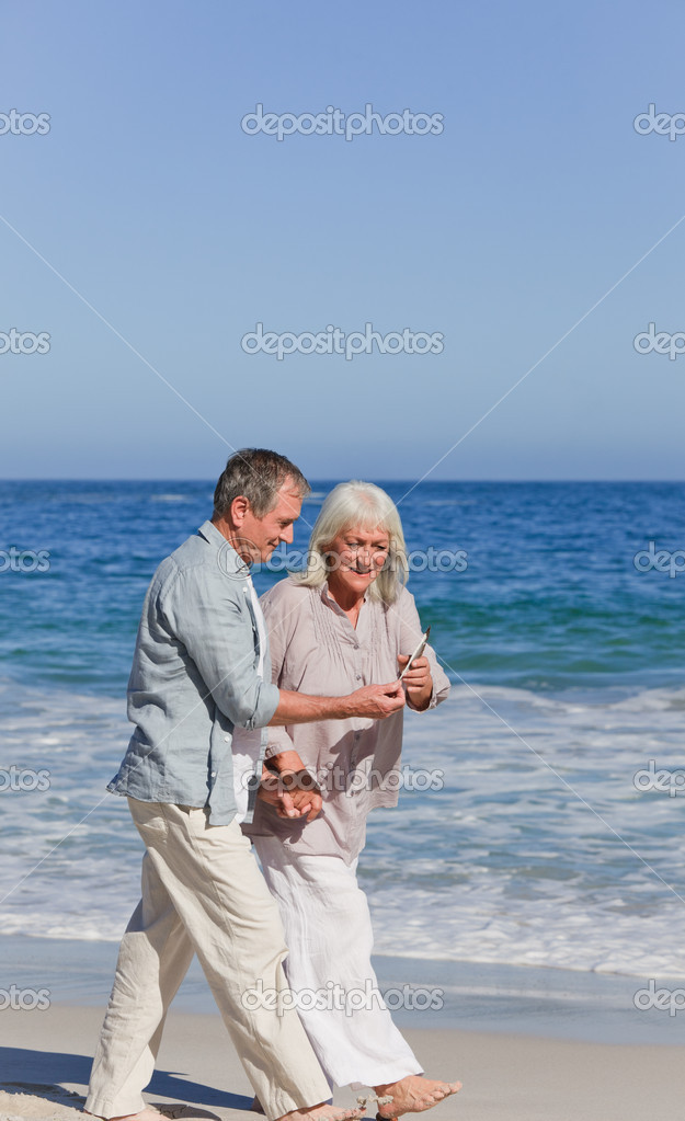 Elderly couple walking on the beach — Stock Photo #10853059